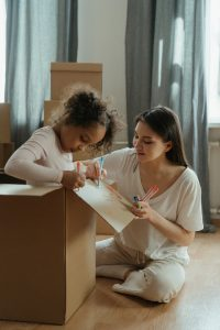 A mother and daughter packing boxes for a move.