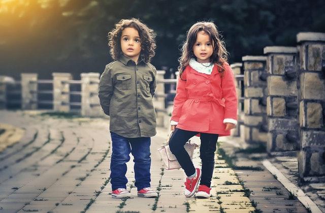 Children standing near a fence.