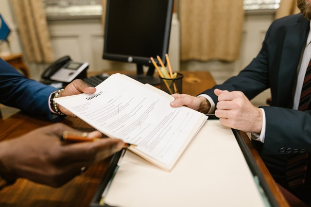 A person holding a pen and paper and giving it to another person to sign.