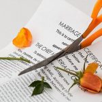 A pair of scissors cutting a marriage certificate and an orange rose