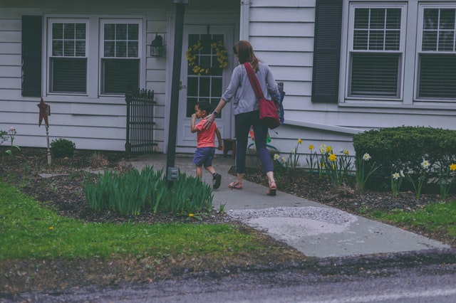 A woman entering a house with her son